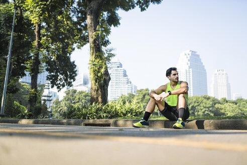 Runner talking a break, sitting on curbstone - SBOF01115