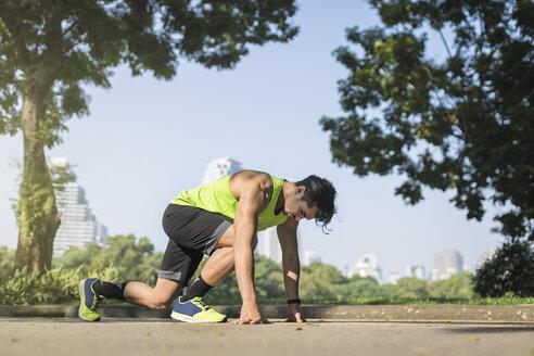 Runner training start position on street in urban park - SBOF01136