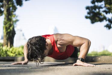 Athlete doing push-ups in urban park - SBOF01142