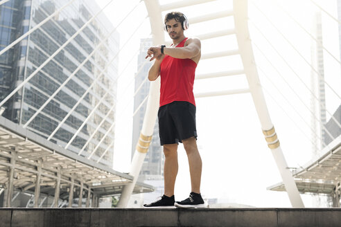 Athlete with earphones checking his smartwatch - SBOF01145