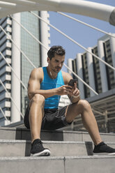 Runner wearing earphones, checking messages on his smartphone - SBOF01151