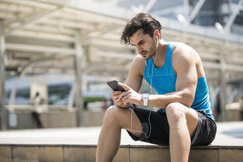 Runner wearing earphones, checking messages on his smartphone - SBOF01169