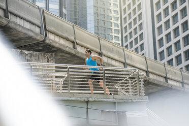 Runner in blue fitness shirt running over modern bridge - SBOF01175