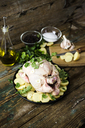 Uncooked chicken with parsley and potatoes in baking pan - GIOF03729