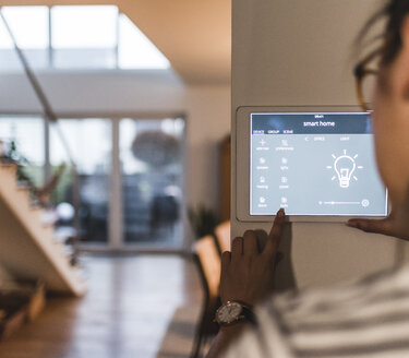 Woman using screen with smart home control functions at home - UUF12497