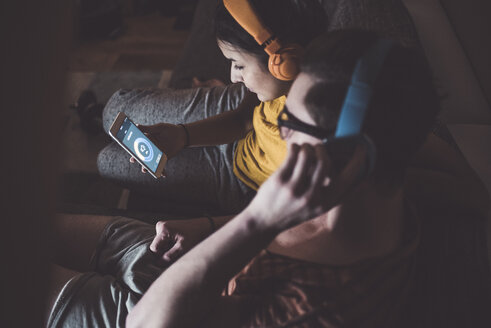 Couple listening to music with headphones and smartphone at home - UUF12509