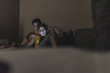 Couple with headphones and tablet relaxing on couch at home - UUF12512