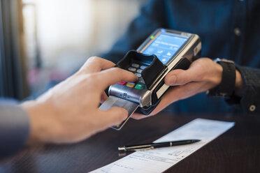 Man using credit card reader, close-up - DIGF03215