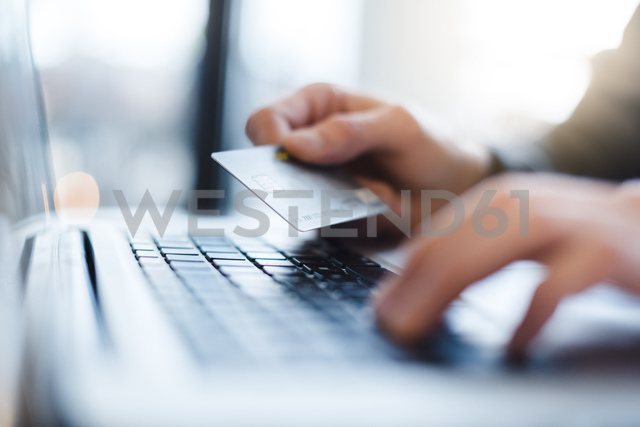 Man using laptop and holding credit card, close-up - DIGF03218 - Daniel Ingold/Westend61