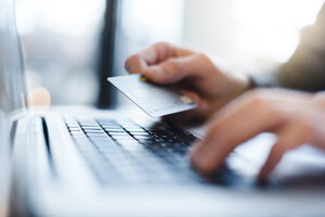Man using laptop and holding credit card, close-up - DIGF03218