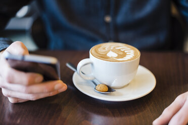 Man using cell phone in a coffee shop, close-up - DIGF03221