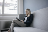 Smling businesswoman sitting on the couch using tablet - JOSF02090