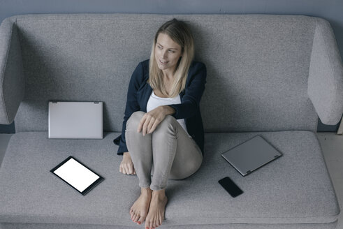 Smiling businesswoman sitting on the couch with several electronic devices relaxing - JOSF02093