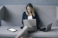 Smiling businesswoman sitting on the couch using laptop - JOSF02099
