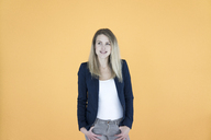Portrait of smiling businesswoman in front of yellow background - JOSF02102