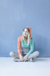 Portrait of smiling woman wearing hooded jacket sitting on the floor in front of blue wall - JOSF02108