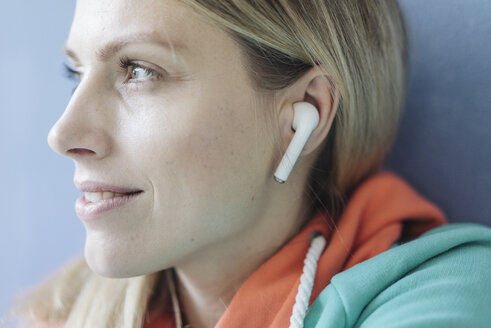 Portrait of smiling woman listening music with wireless earphones, close-up - JOSF02111