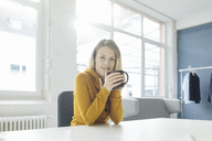 Portrait of fashion designer sitting at desk in her studio with cup of coffee - JOSF02114