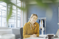 Portrait of smiling fashion designer sitting at desk in her studio - JOSF02123