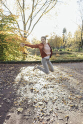 Happy young woman jumping in the air in autumnal park - JOSF02150