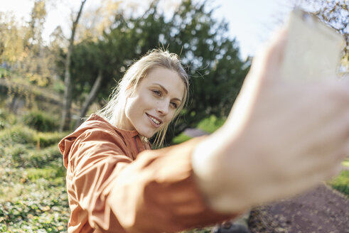 Portrait of young woman taking selfie with cell phone in autumnal park - JOSF02153