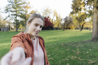 Portrait of young woman reaching out hand in autumnal park - JOSF02156