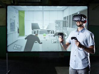 Smiling man wearing VR glasses in front of screen - CVF00016