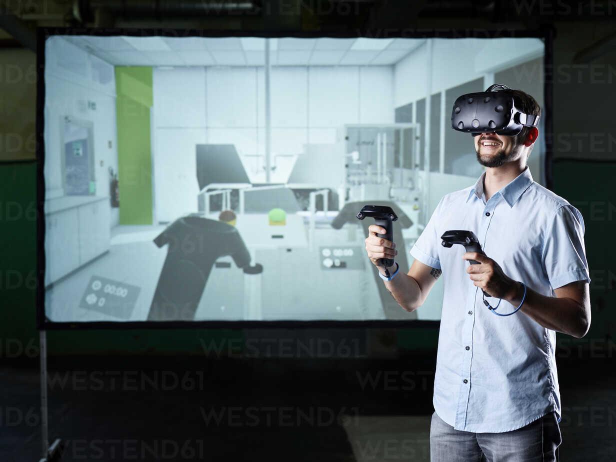 Lächelnder Mann mit VR-Brille vor dem Bildschirm - CVF00016 - Christian Vorhofer/Westend61