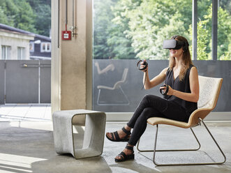 Smiling woman wearing VR glasses sitting on chair - CVF00019