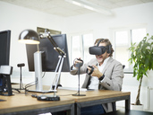 Happy man wearing VR glasses at desk in office - CVF00022
