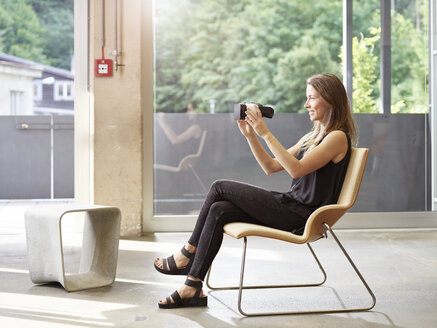 Woman holding VR glasses sitting on chair - CVF00025