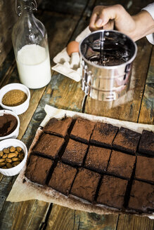 Woman's hand sprinkling cacao on brownies - GIOF03745