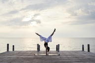 Young woman practicing yoga on a jetty by the sea at sunset - IGGF00392