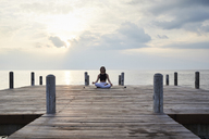Young woman practicing yoga on a jetty by the sea at sunset - IGGF00395