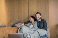 Laughing young couple relaxing together on the couch - FMKF04684