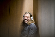 Portrait of laughing man listening music with headphones - FMKF04687