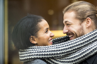 Portrait of happy young couple sharing scarf - FMKF04696