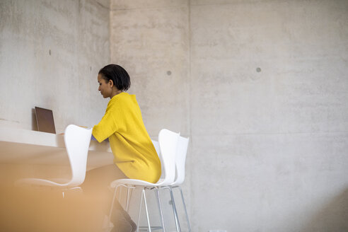 Young woman wearing yellow pullover using laptop - FMKF04708