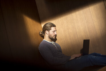 Portrait of young man using laptop - FMKF04717