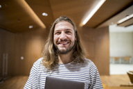 Portrait of laughing man with laptop in university - FMKF04741