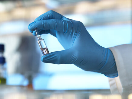 Scientist holding a vial containing a liquid in the laboratory - ABRF00020