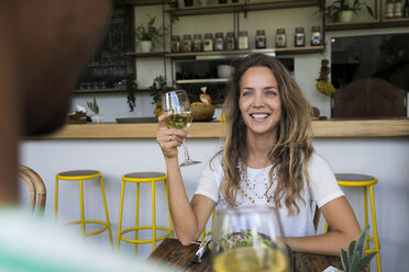Smiling woman with glass of wine looking at man in a cafe - SBOF01177
