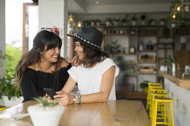 Two female friends smiling at each other in cafe with smartphone - SBOF01192