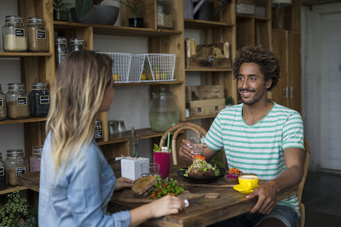 Smiling couple enjoying a meal together in cozy restaurant - SBOF01195