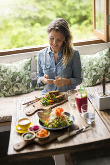 Woman taking a picture of food with smartphone in cozy cafe in front of window - SBOF01198