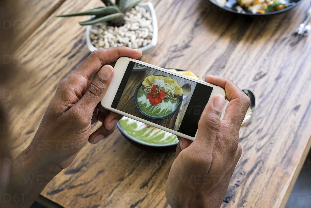 Male hands taking a picture of smoothie bowl with smartphone - SBOF01213 - Steve Brookland/Westend61