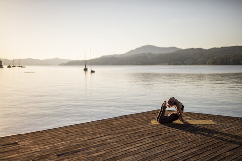 Woman practicing yoga on jetty at a lake - DAWF00567
