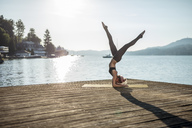 Woman practicing yoga on jetty at a lake - DAWF00579