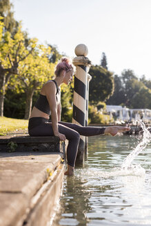 Woman in sportswear sitting at lakeshore with feet in water - DAWF00588