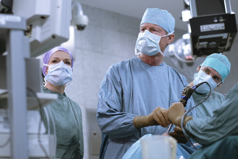 Team of neurosurgeons in scrubs during an operation - MWEF00187